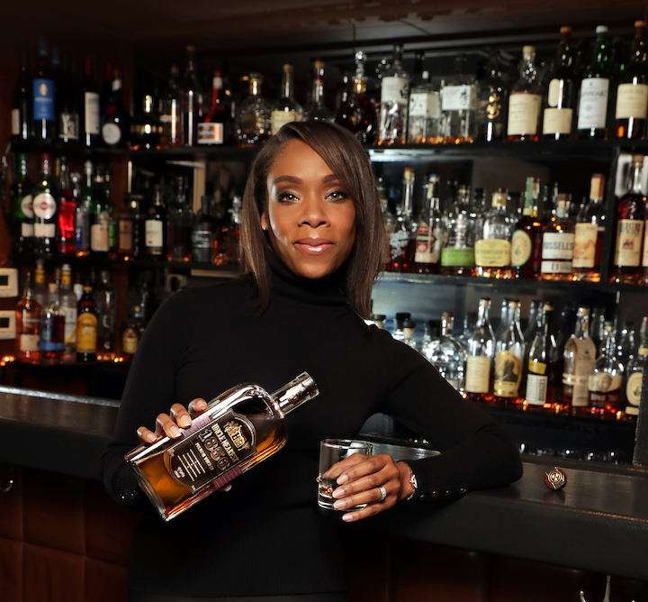 Fawn Weaver, CEO and Master Distiller of Uncle Nearest Premium Whiskey posing while leaning on a bar and pouring a glass of whiskey